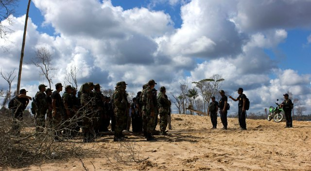 Police officers in fatigues stand on pitted, sandy ground