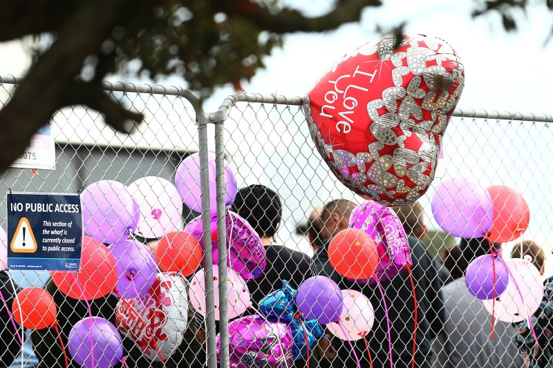 A heart shaped balloon saying I love you shown tied to a fence with other balloons.