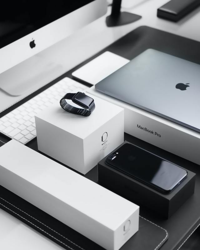 An apple computer, laptop, watch and phone sit on their boxes in a neat order