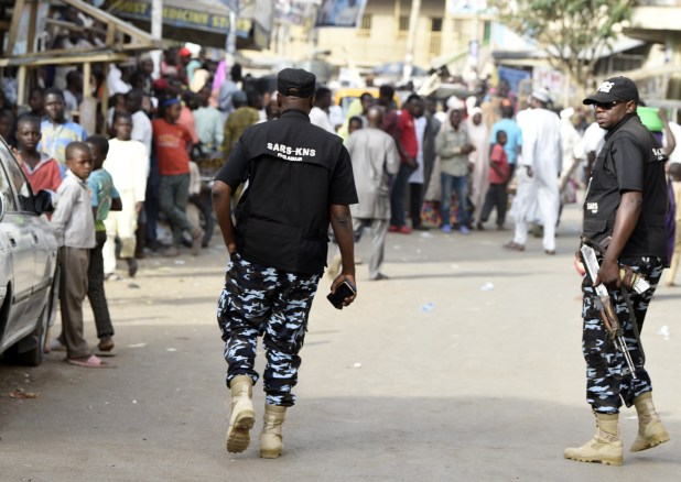 Heavily armed men in camouflage and black vests walk toward a line of voters