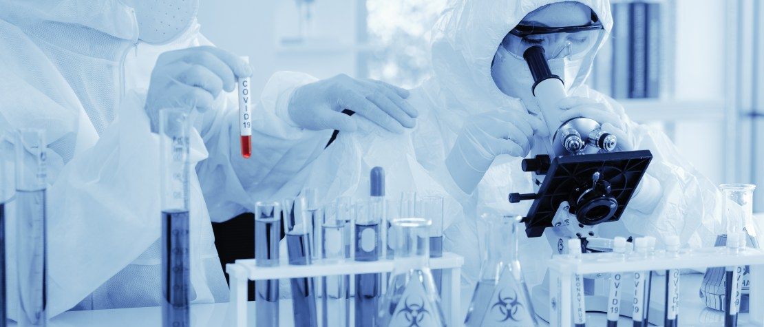 Scientist in biohazard protection clothing analysing a COVID-19 sample with microscope.