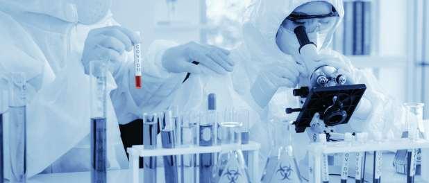 عالم في ملابس الحماية من المخاطر البيولوجية يحلل عينة COVID-19 بالمجهر.