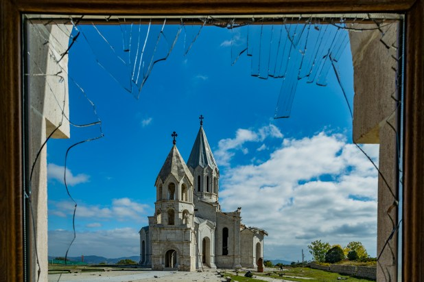 View of a damaged cathedral from a broken glass window