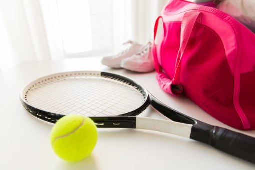 Tennis bag, racket, ball and shoes lying around at home