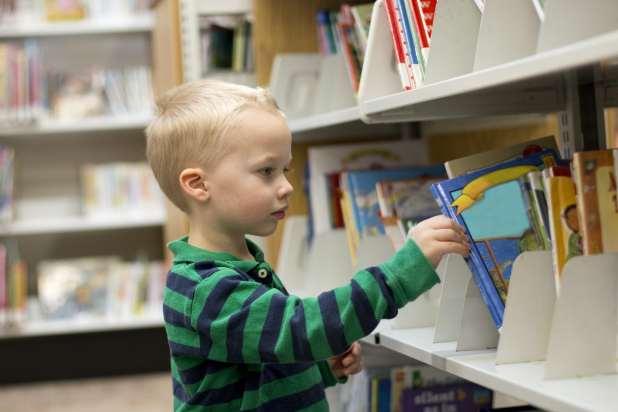 Little boy picking a book off a library shelf