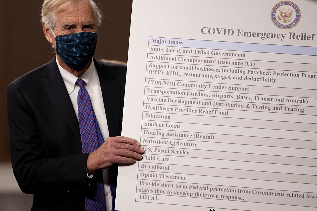 Maine Independent Sen. Angus King sets up a sign describing a bipartisan proposal for a Covid-19 relief bill on Capitol Hill.
