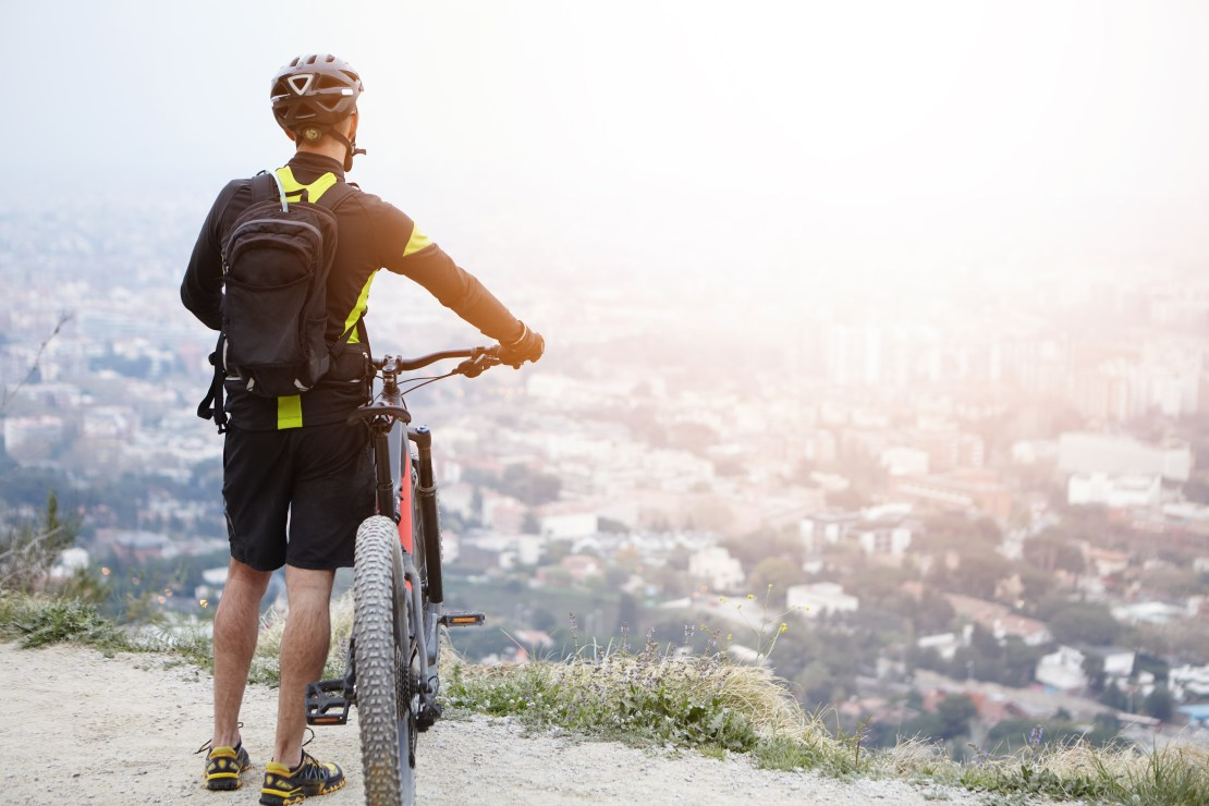 A man with a bike looks out on a city below him.