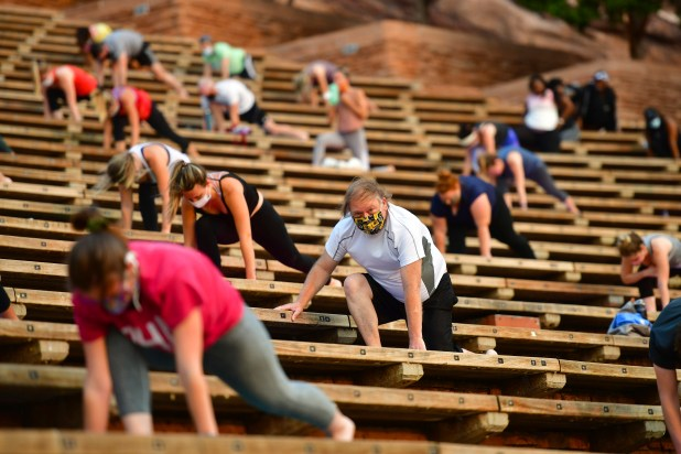 people stretching while socially distanced in stadium seats