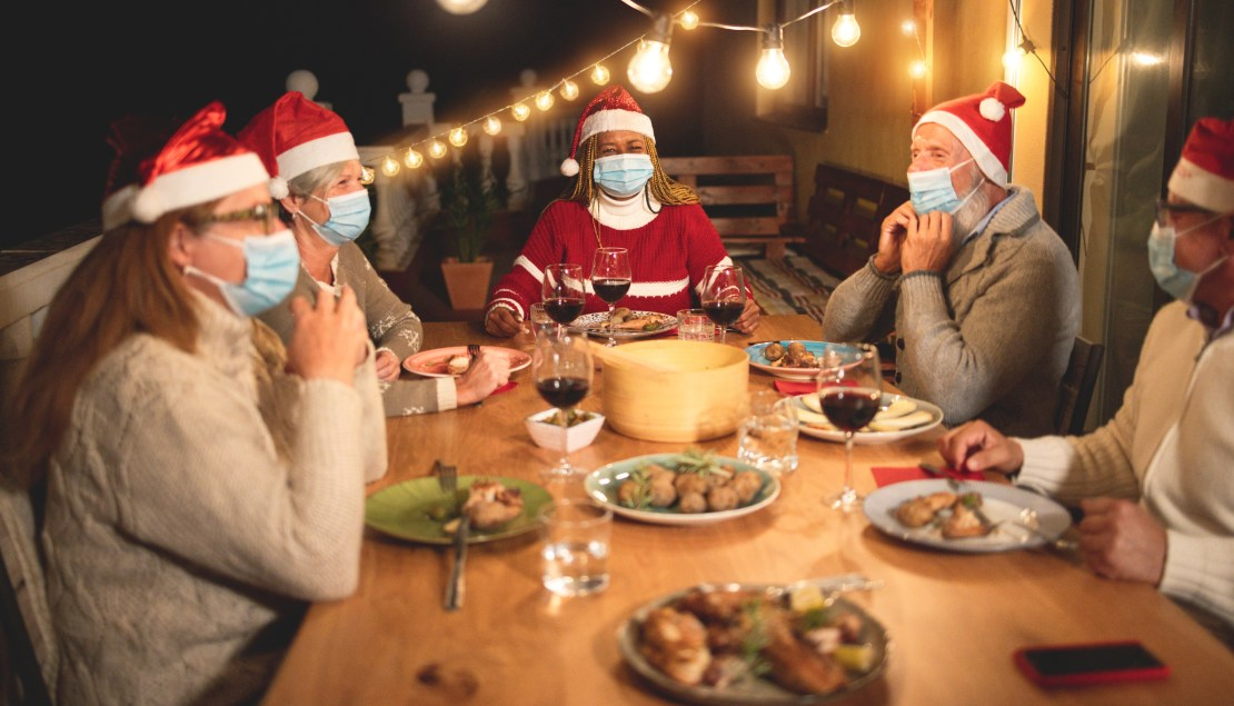 A family eating Christmas dinner wearing masks.