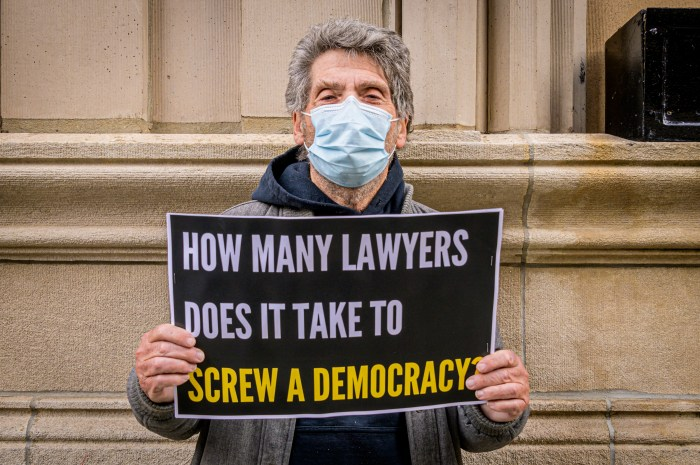 A protestor outside Giuliani's apartment building with a sign that says 'How many lawyers does it take to screw a democracy'