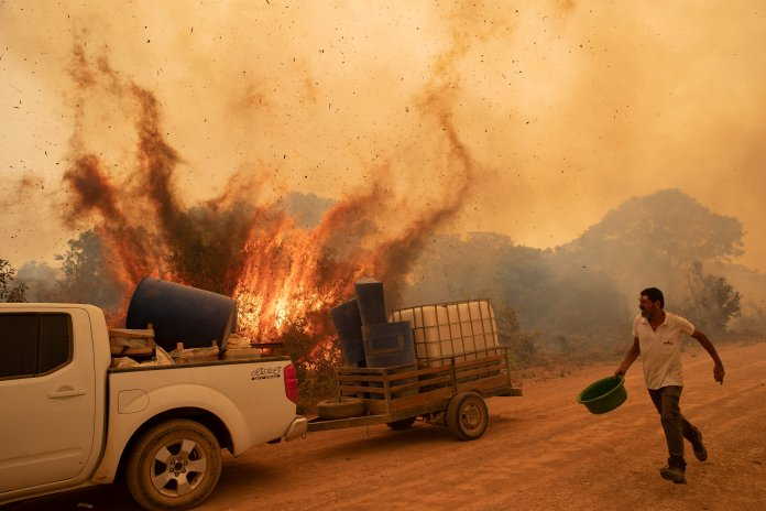 A man running with a bucket near a fire and a pickup truck.