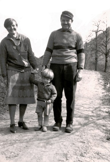 A black and white picture of parents and a child.
