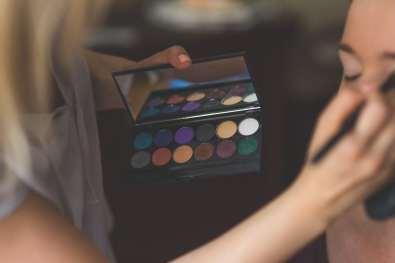A makeup artist applies eye shadow to another woman.