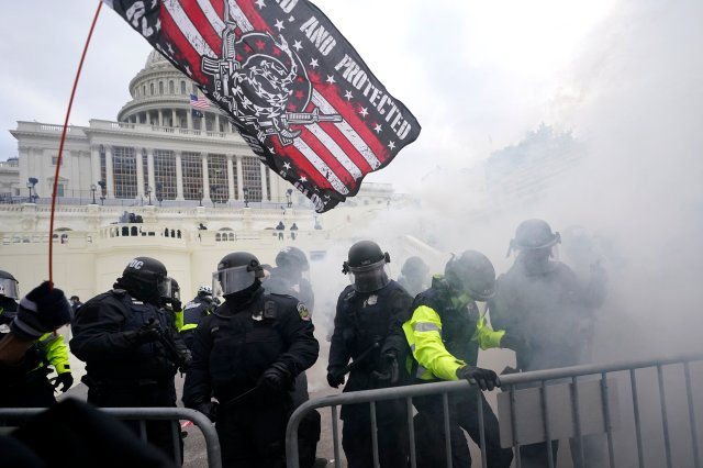 Police in riot gear are behind a metal barricade in front of the Capitol dome