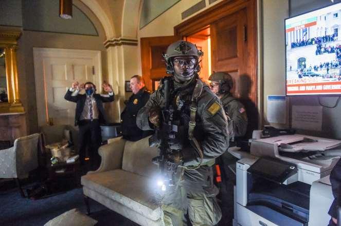 Ein Kongressmitarbeiter hält seine Hände hoch, während das SWAT-Team der Capitol Police ein Büro räumt