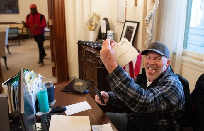 Richard Barnett sits at a desk holding a piece of mail with Nancy Pelosi's name and sticking his tongue out.