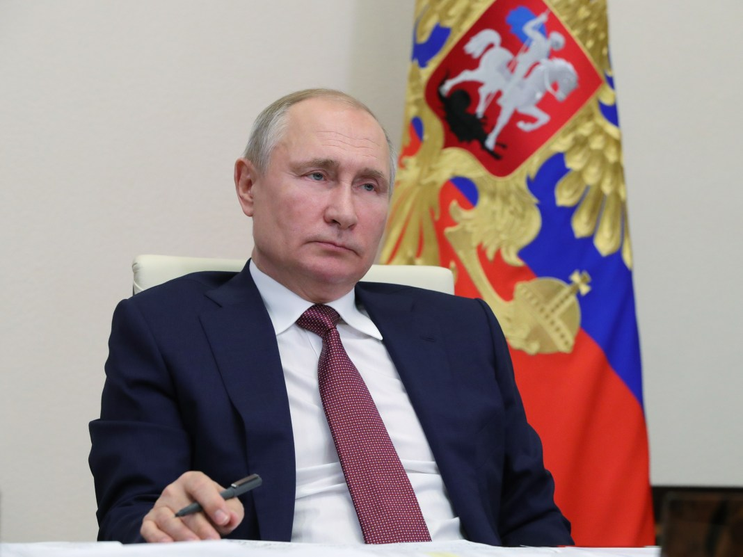 Vladimir Putin sits with pen in his hand in front of a Russian Federation flag.