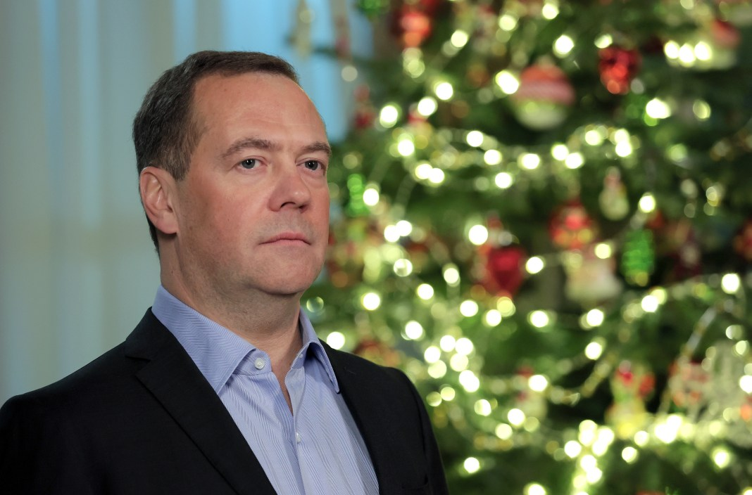Dmitry Medvedev, a middle-aged Russian politician, poses in front of a Christmas tree.