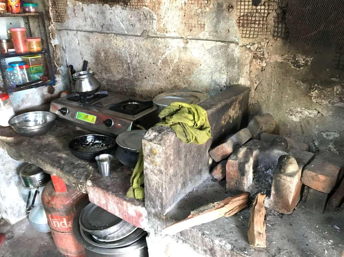 Metal stove on brick shelf with kerosene tank below.