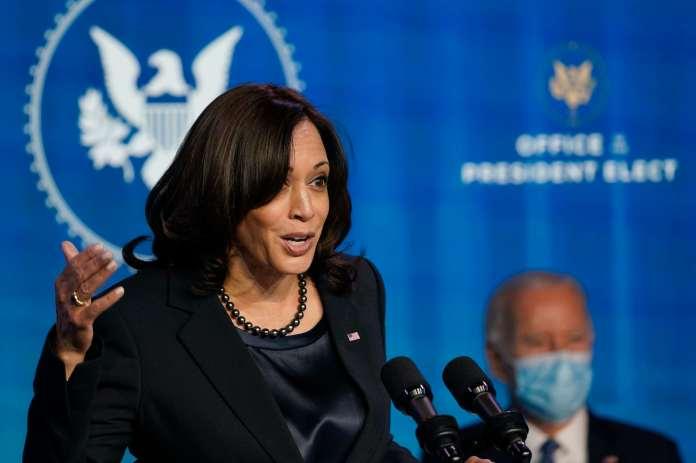 Kamala Harris delivers a speech. Joe Biden is sitting in the background.