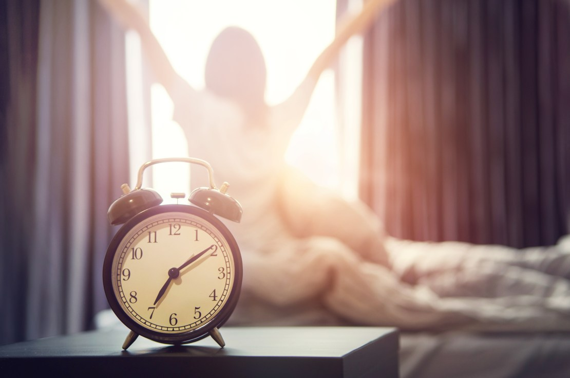A woman being woken up by an alarm clock on a sunlit morning