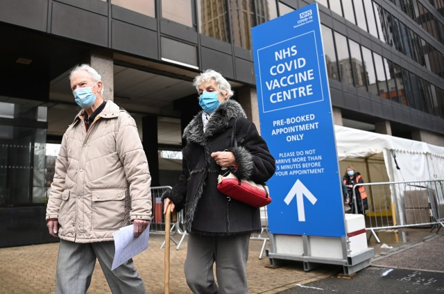 A UK couple leave a COVID vaccine centre in London.