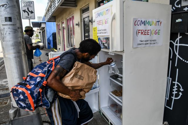 People taking free food from a community refrigerator.