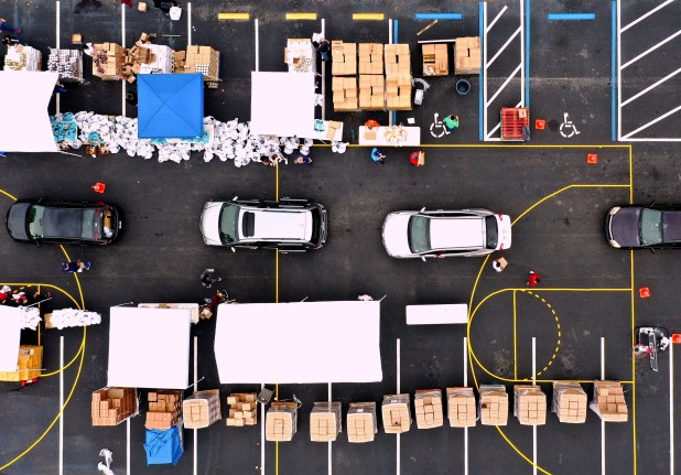 An aerial view shows volunteers loading cars with turkeys and other food.