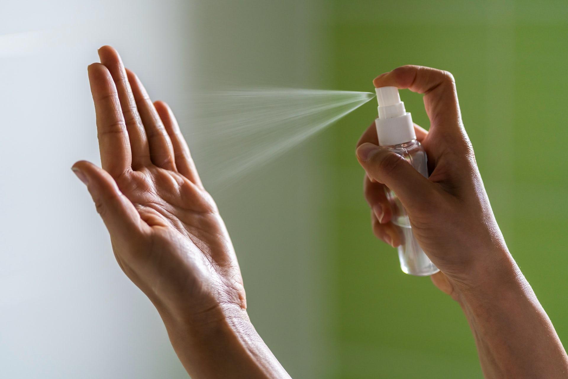 Una persona pulveriza sobre una de sus manos un gel hidroalcohólico.
