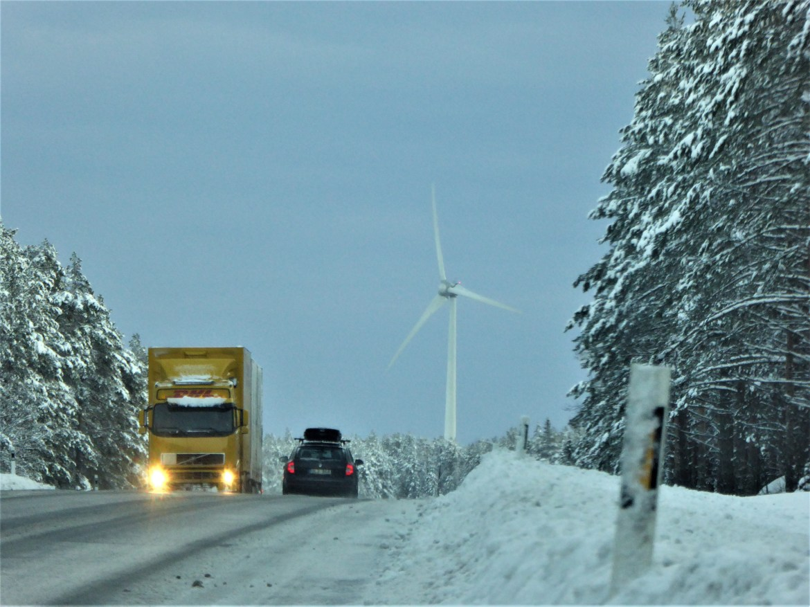 A snowy road traversed by a lorry and van with a wind turbine in the background.