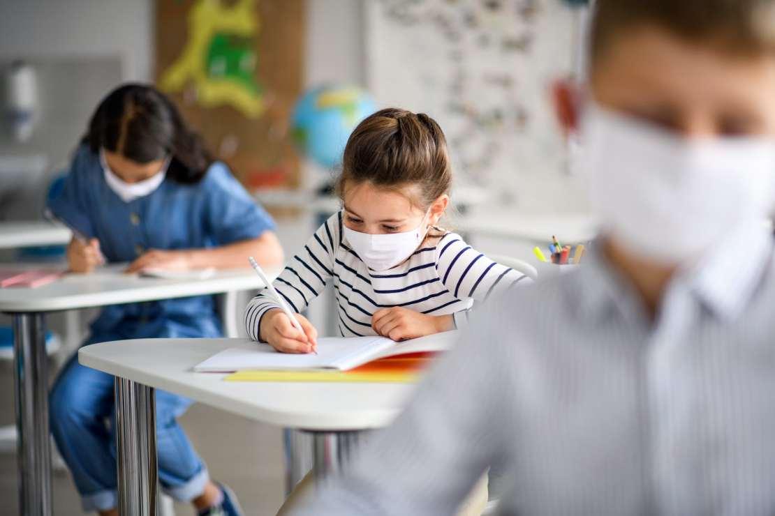 Children wearing masks write during class.
