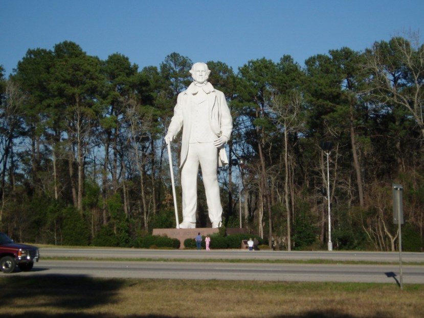 A giant white marble statue of a man with a cane, highway in the foreground