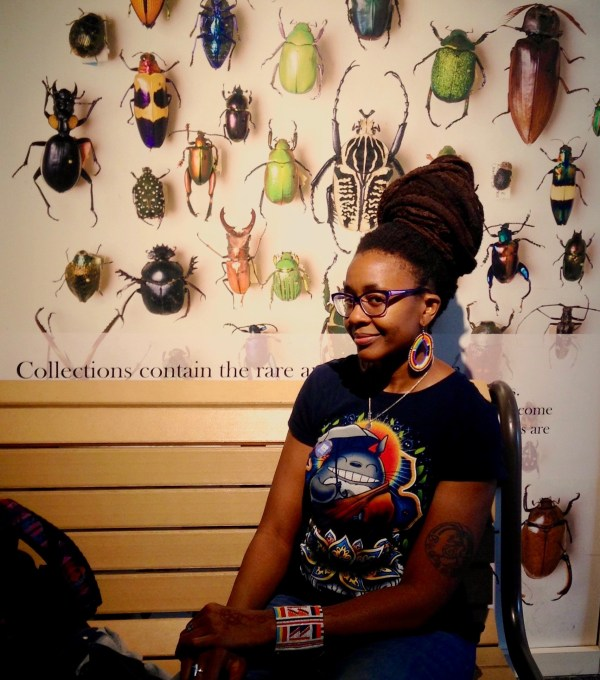 A woman with a wry smile and large hairstyle sits in front of a museum display of insects.