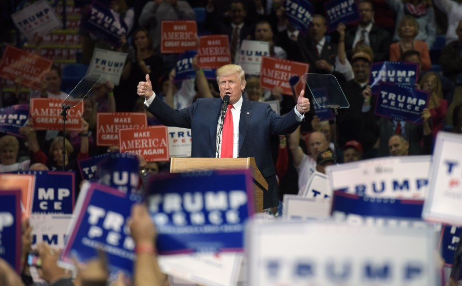 Donald Trump en un mitin con multitudes y pancartas