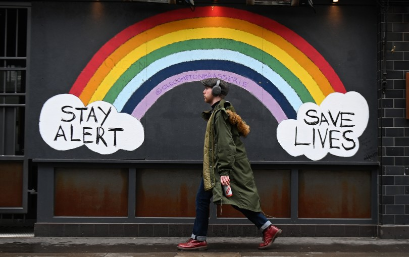 A man walks past a mural of a rainbow and two clouds saying 'Stay Alert' and 'Save Lives'