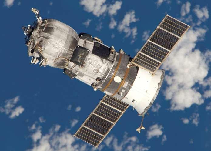 Le vaisseau spatial russe Progress flottant au-dessus de la Terre. Il est cylindrique avec deux panneaux solaires dépassant sur les côtés