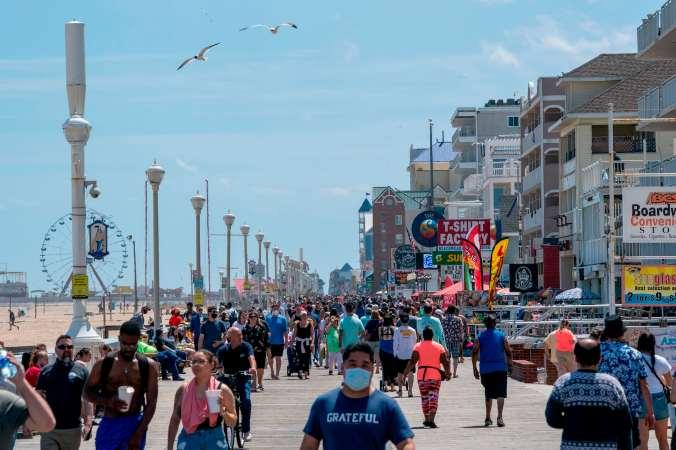 Vistors, many without masks, walk the beachfront boardwalk