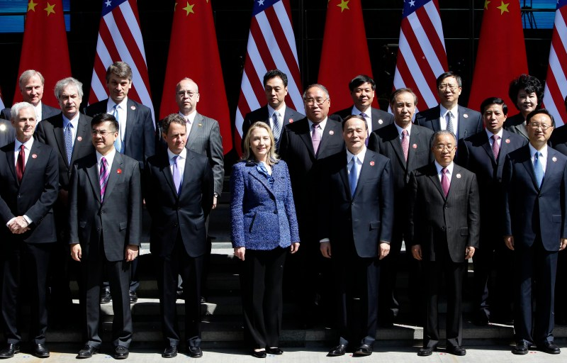 Clinton, in a blue blazer, stands at the center of a large group of Chinese and American diplomats posing for a picture, all wearing black suits
