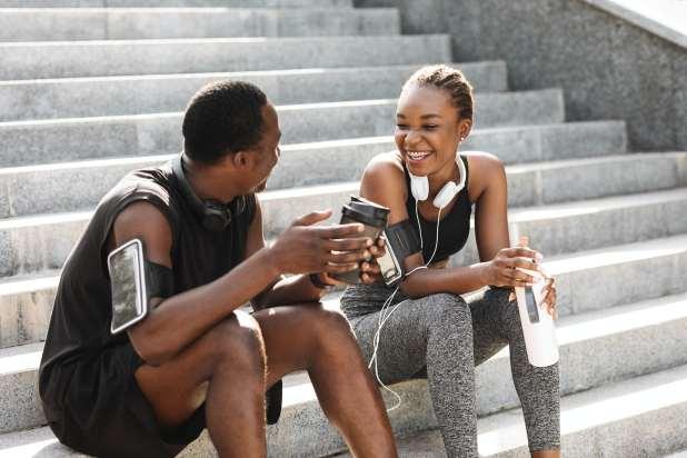 شاب وشابة يرتديان ملابسهما الرياضية يتوقفان بعد التمرين لشرب الماء والقهوة.