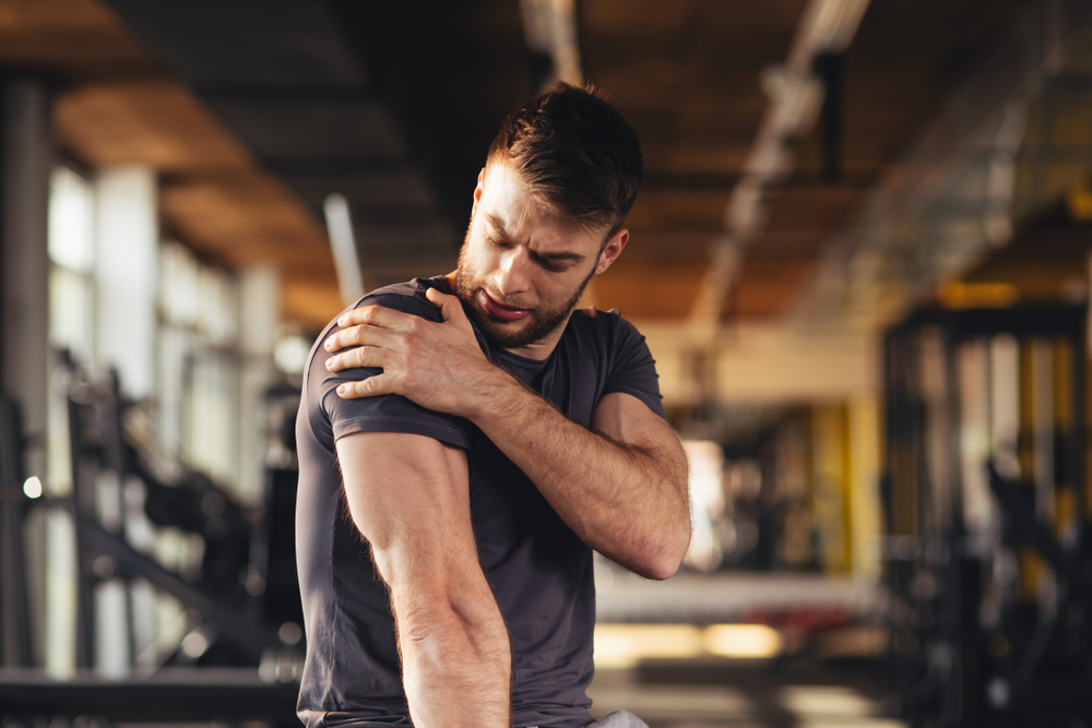 Man holding is shoulder in pain at the gym