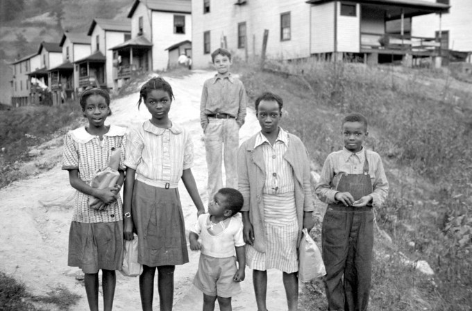 Five Black children stand in the foreground while a white boy stands in the background.