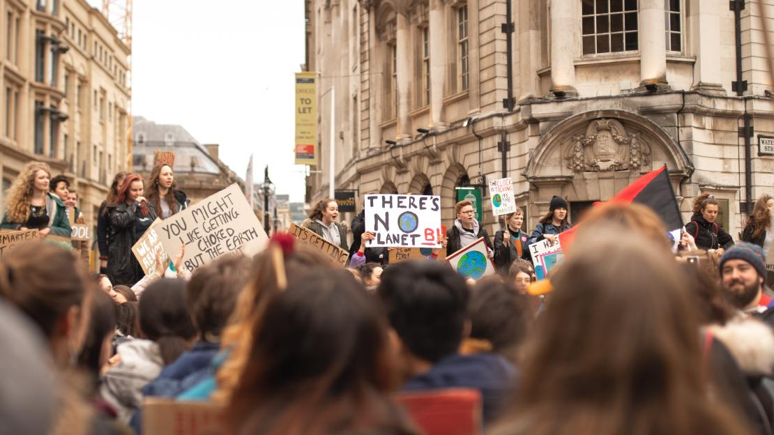 Crowds of young people hold placards.