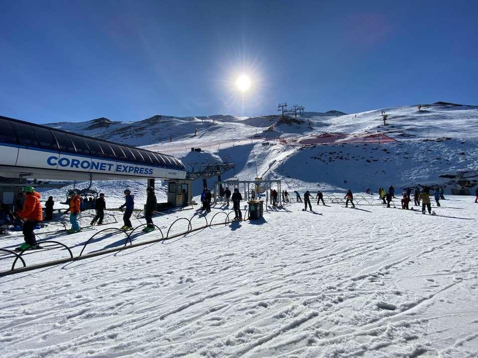 Skiers on mountain skifield in sunlight