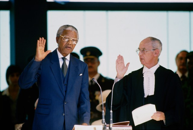 Mandela holds his right hand in the air, next to a judge