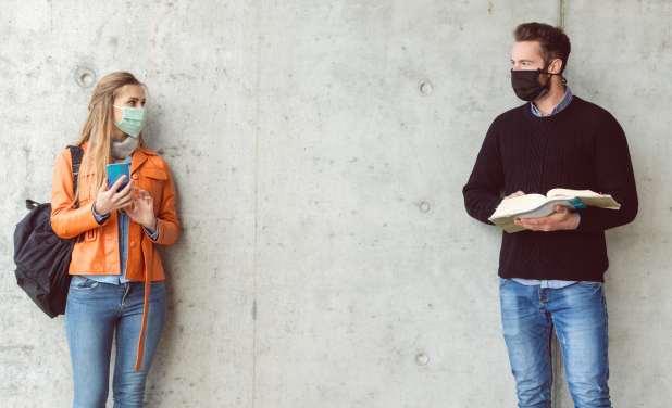 رجل وامرأة في حرم جامعي يرتديان أقنعة