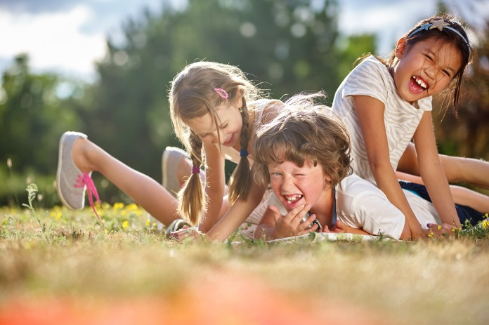 Three children laughing in a bundle on some grass