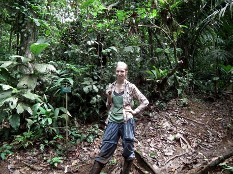 Woman standing in the middle of a rainforest.