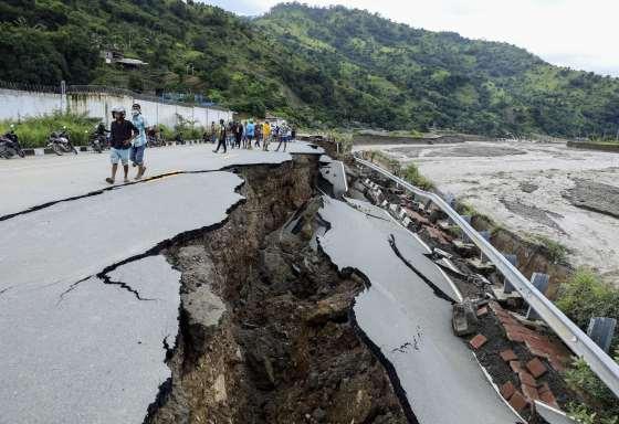 Sebuah jalan runtuh setelah banjir
