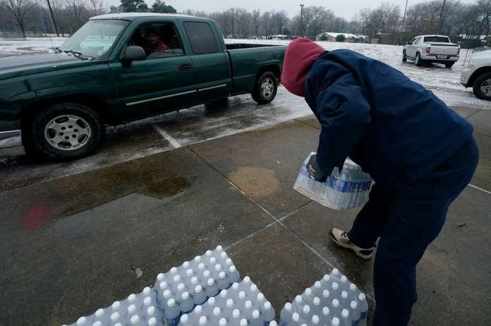 A city worker loads bottled water into a pickup truck.