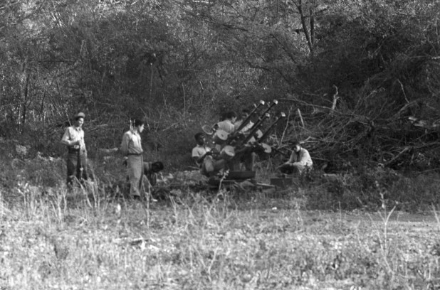 Black-and-white image of militiamen with weapons in a field